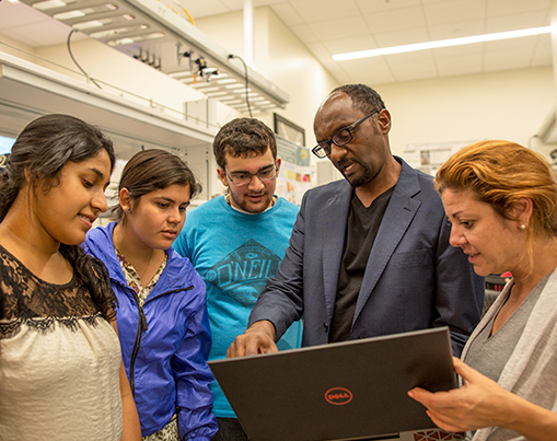 Professor showing students something on his laptop